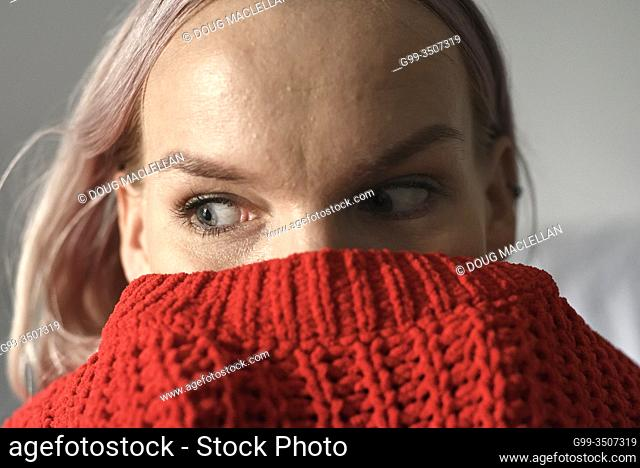 A woman with light pink hair posing with a red sweater up to her eyes in the autumn in Canada