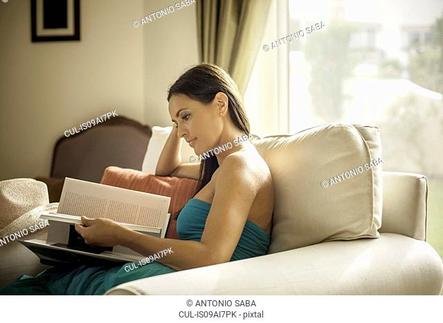 Young woman sitting in armchair reading book