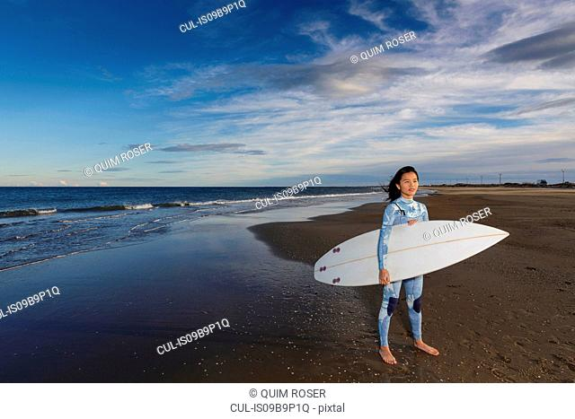 Portrait of young female surfer standing on beach, Tarragona, Catalonia, Spain