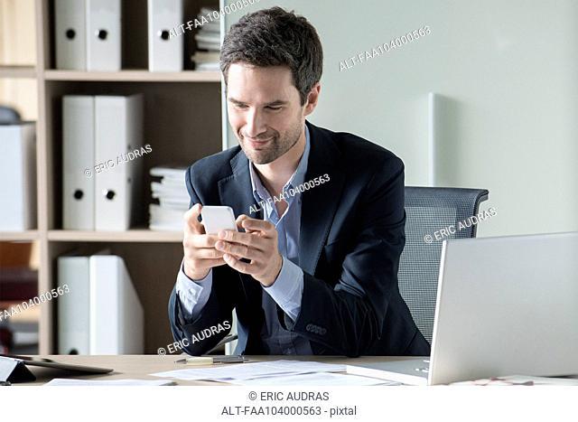 Businessman text messaging
