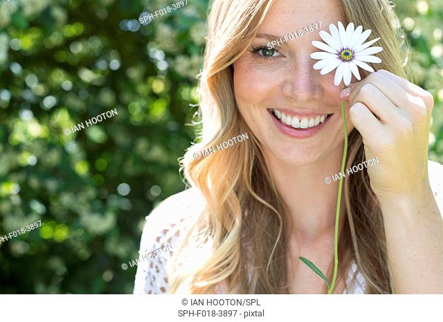 MODEL RELEASED. Young woman holding daisy in front of eye