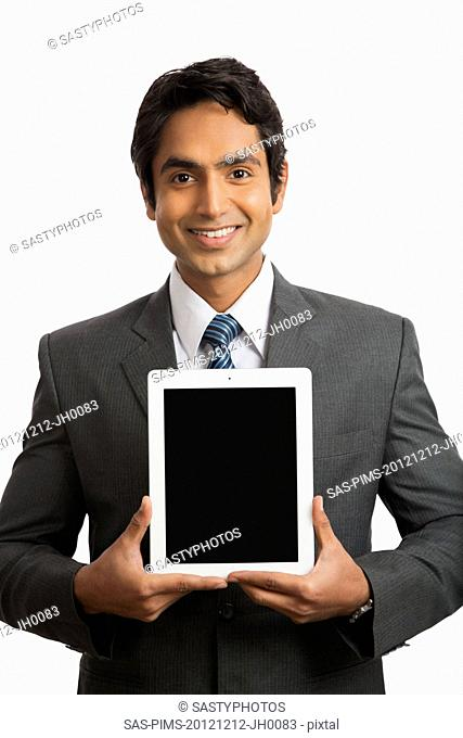 Portrait of a smiling businessman holding a digital tablet