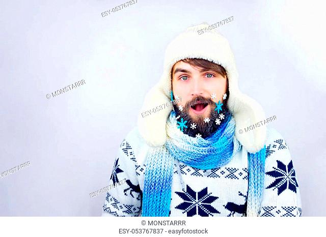 Guy with trapper hat and blue scarf wearing beard decorated with small snowflakes, being surprised