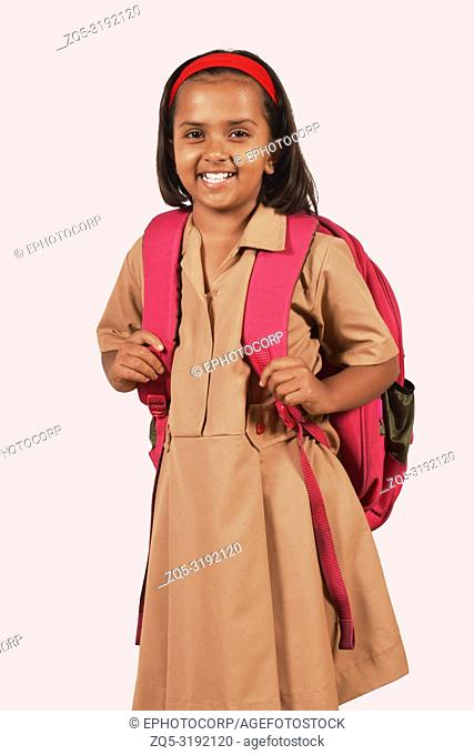 Little girl in school uniform and bag posing in front of camera. Pune, Maharashtra