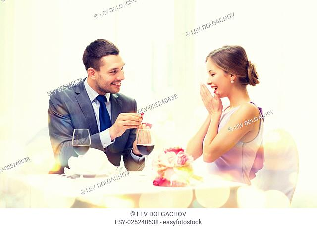 restaurant, couple and holiday concept - smiling man proposing to his girlfriend at restaurant