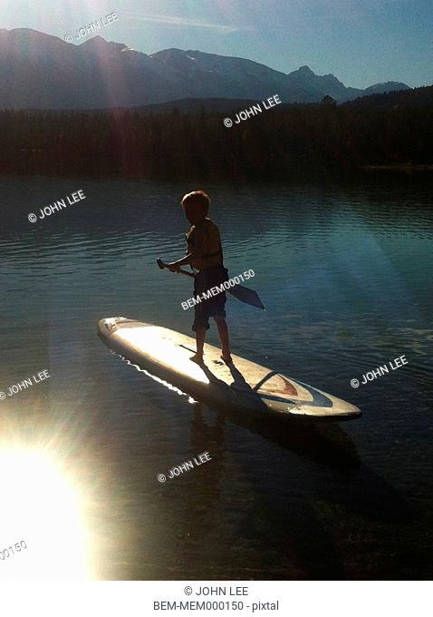 Caucasian boy paddleboarding on lake, Jasper, Alberta, Canada