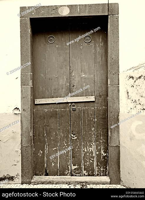 sepia vintage style image of a closed wooden door locked and barred shut with nails with peeling paint and stone surround