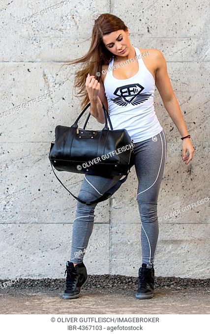 Young woman poses in a sporty outfit with bag, fashion, lifestyle