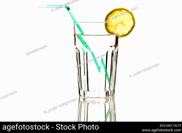 glass of mineral water with green straw and lemon isolated on white