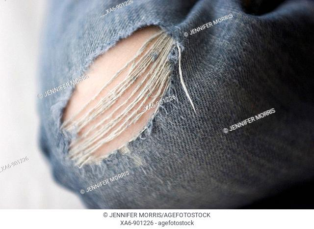 The split and tattered knee of a boy's pair of jeans