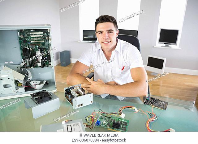 Nice looking computer engineer sitting at desk smiling at camera