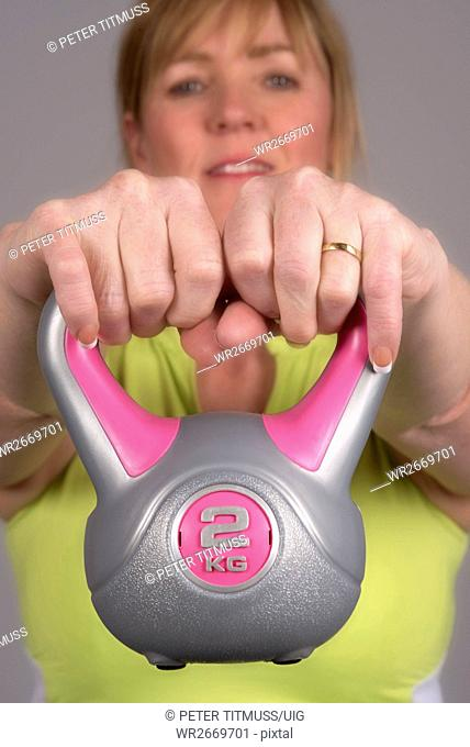 Woman exercising with a kettle bell weight