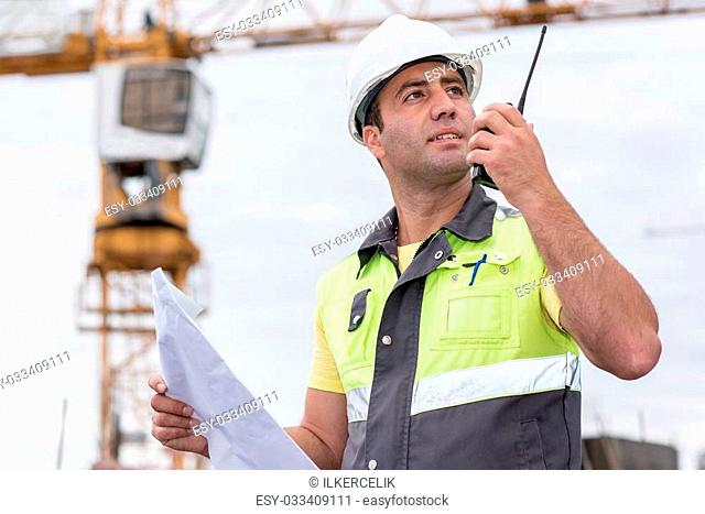Civil Engineer at construction site is inspecting ongoing production according to design drawings
