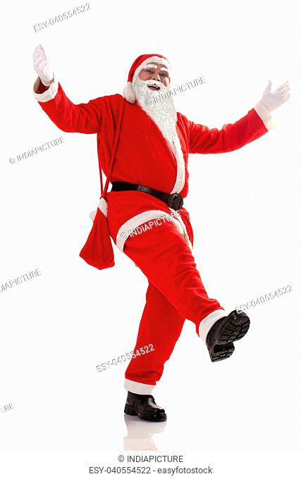 Full length of Santa Claus dancing over white background