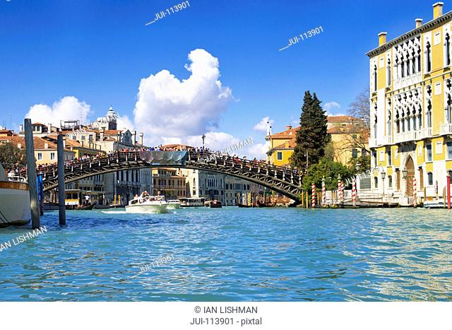 Arch Ponte dell'Accademia bridge over sunny Grand Canal with boats in Venice, Italy