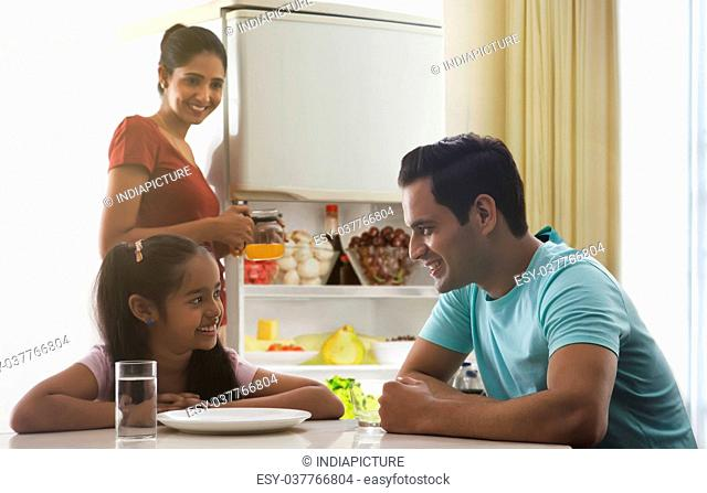 Father and daughter having breakfast while mother storing juice in refrigerator