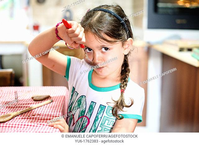 Children lick spoon with chocolate