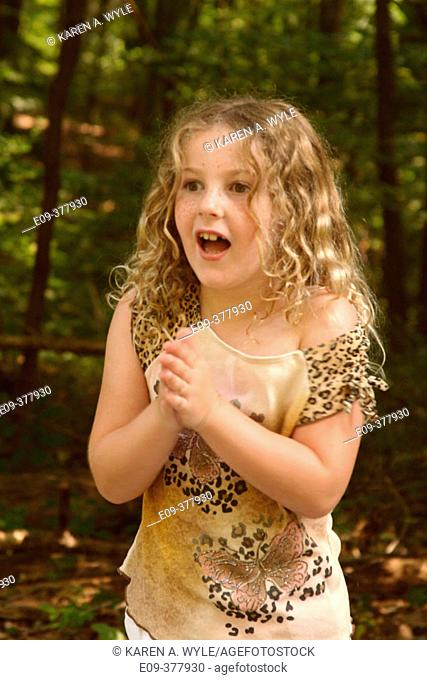 8-year-old girl in short sleeved shirt with excited expression, hands together in clapping, Indiana, USA