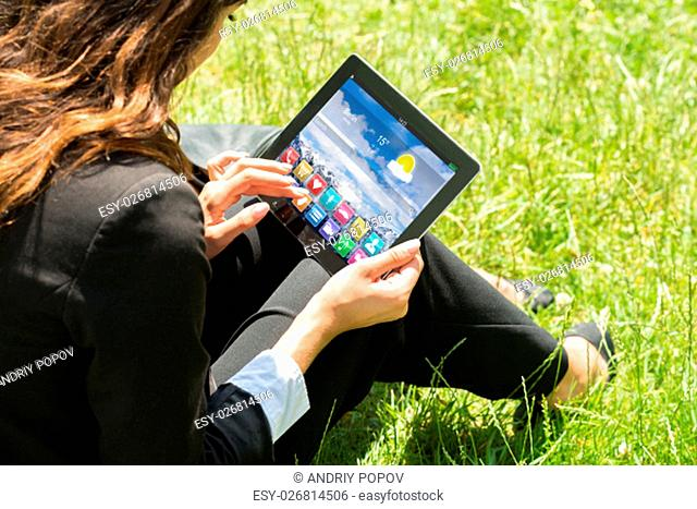 Close-up Of Businesswoman Sitting On Grass Using Digital Tablet With Multicolored Apps On It