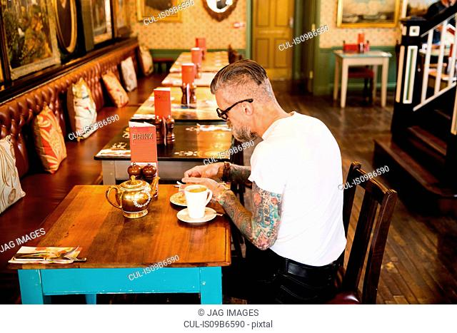 Quirky man eating in bar and restaurant, Bournemouth, England