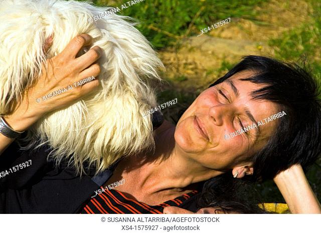 Home, sweet home. Woman lying on grass with greeting bobtail