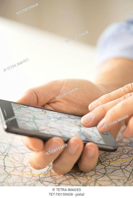 Close-up of hand using smartphone over map