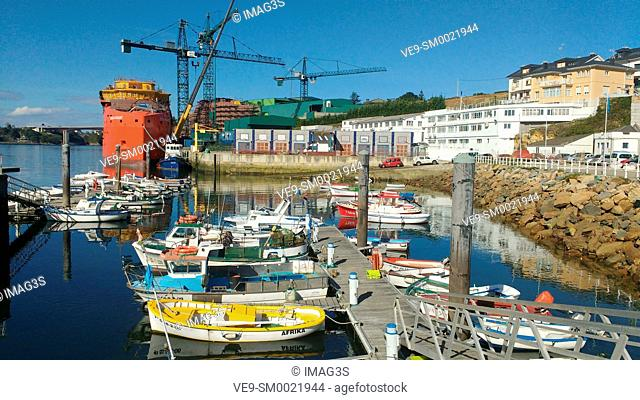 Figueras port and a SOV (Service Operation Vessel), being built at Gondán shipyard in backgound, Asturias, Spain