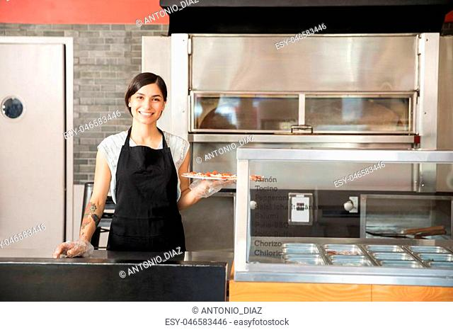 Portrait of smiling chef wearing black apron and hand gloves showing raw pepperoni pizza in commercial kitchen in pizza shop while looking at camera
