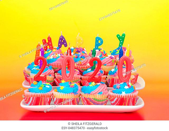 White cupcakes with rainbow colored frosting and brightly colored star candies on rectangular plates pink yellow orange background with Happy 2019 candles...