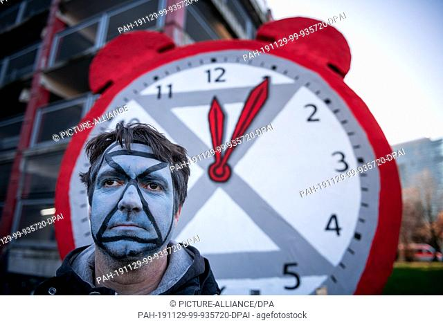 29 November 2019, North Rhine-Westphalia, Duesseldorf: A demonstrator stands in front of a clock with its hands set at five past twelve