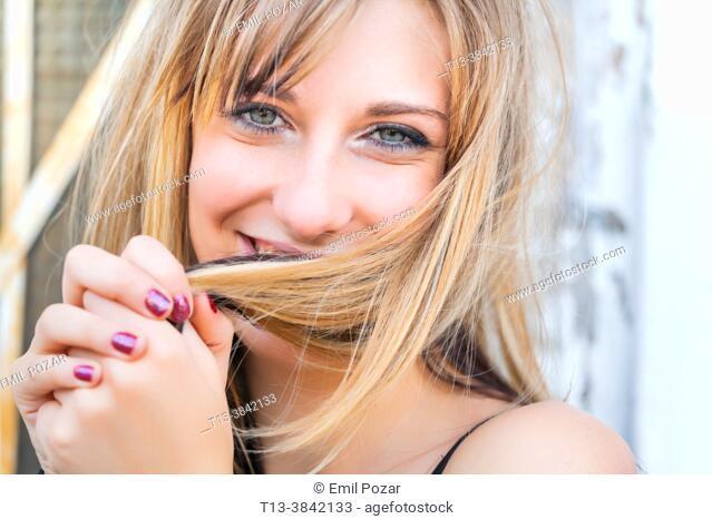 Teen girl headshot close-up shy behind messy hair
