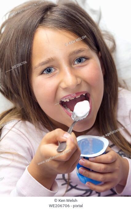 Six years old girl eating yoghurt