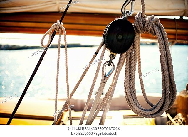 Foreground of pulley and ropes and the boom and mainsail in the background of a vintage yacht moored at Port Mahón, Menorca, Balearic Islands, Spain, Europe