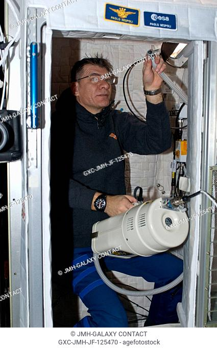 European Space Agency astronaut Paolo Nespoli, Expedition 26 flight engineer, uses a vacuum cleaner during housekeeping operations in his crew quarters...