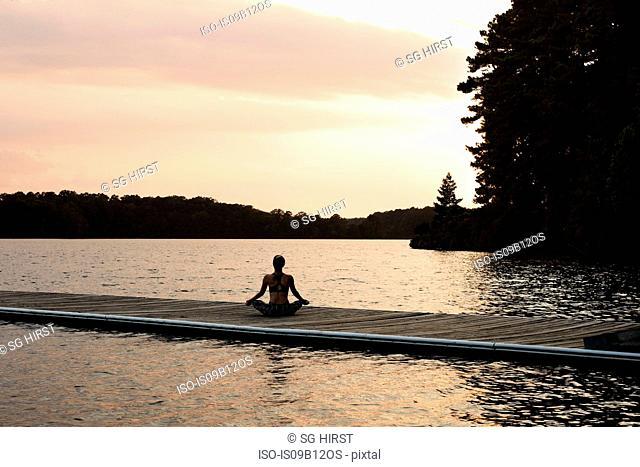 Rear view of woman on pier by lake meditating, North Carolina, USA
