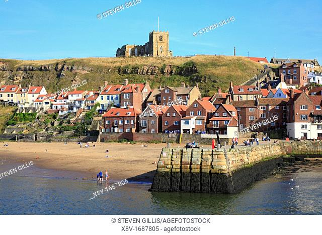 St Mary's Church on East Cliff above Fishermens cottages and Tate Hill Pier, Lower Harbour, Whitby, North Yorkshire, England, UK