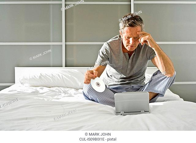 Senior man sitting up holding CD and staring at laptop