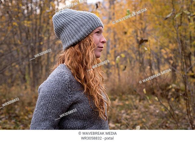Woman in warm clothing standing in the autumn forest