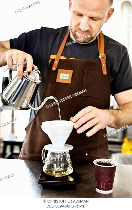 Male barista pouring boiling water into coffee filter