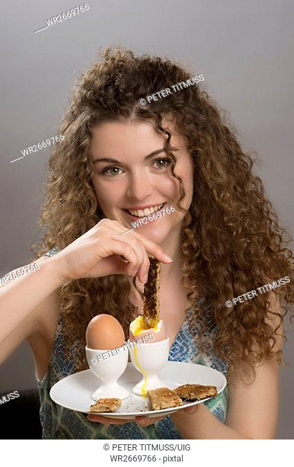 Young girl dipping a slice of toast into boiled eggs for breakfast