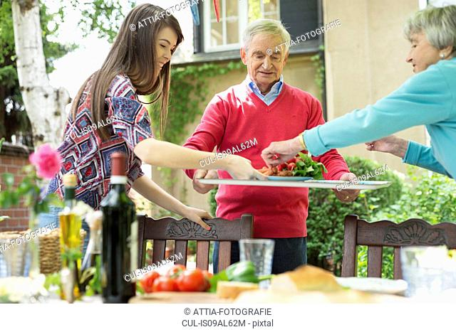 Young woman with grandparents setting the table