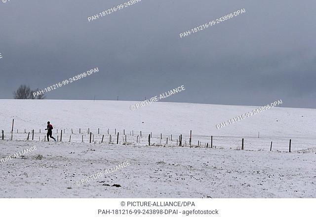 16 December 2018, Bavaria, Marktoberdorf: A jogger walks through the snow-covered landscape. Photo: Karl-Josef Hildenbrand/dpa