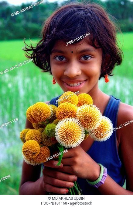Portrait of a smiling girl holding Kadam flowers It grows on the tree Anthocephalus cadamba tree The blooming of Kadam flowers herald the arrival of rainy...