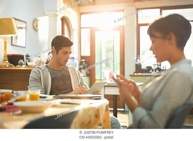 Young couple college students using cell phone and digital tablet at kitchen table