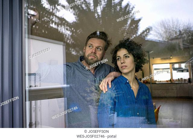 Serious couple behind window at home looking out