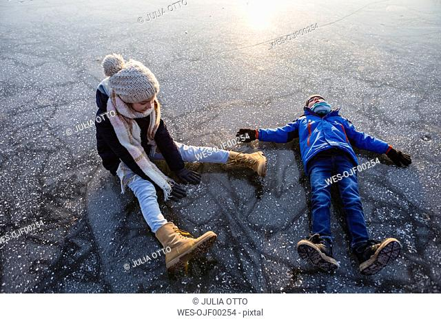 Germany, Brandenburg, Lake Straussee, two kids sitting and lying down on frozen lake