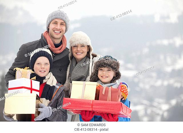 Portrait of happy family with Christmas gifts in snow