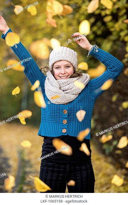 Teenage girl in an Autumn forest inside swirling foliage, Hamburg, Germany, Europe