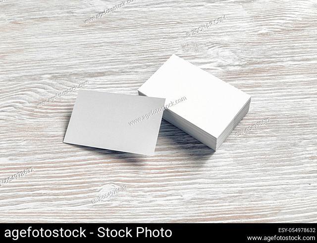 Blank white business cards on light wooden background. Mockup for branding identity
