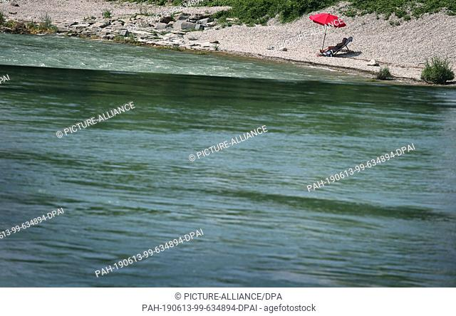 13 June 2019, Bavaria, Landsberg am Lech: A woman on the banks of the Lech enjoys the summer temperatures under a red parasol